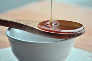 Pouring pure argan oil to a wooden spoon