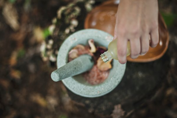 A hand pouring argan oil into a mortar and pestle with rose petals