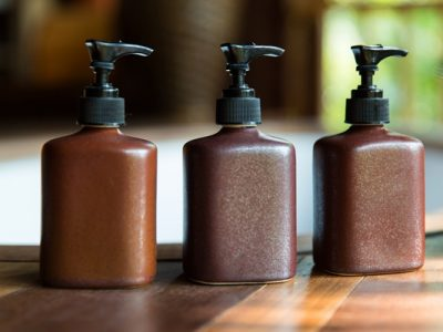 Bottles of argan oil shampoo and conditioner products on a wooden table