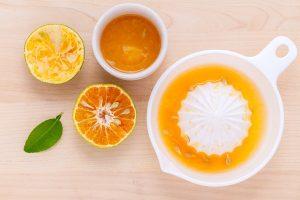 Ingredients for argan oil face toner on wooden surface; a blend of lemon juice, argan oil, and green tea
